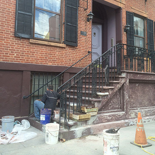 person repairing steps in front of an historic stone home